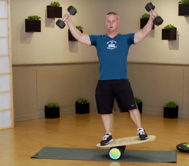 Баланс борд: упражнения — Подъем гантелей в стороны.